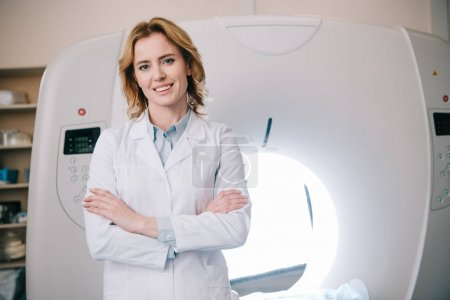 Photo for Cheerful radiologist standing with crossed arms near computed tomography scanner and looking at camera - Royalty Free Image