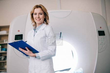Photo for Smiling radiologists writing on clipboard while standing near computed tomography scanner - Royalty Free Image