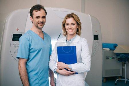lächelnde Ärzte, die in die Kamera schauen, während sie in der Nähe des Computertomographen stehen