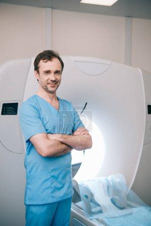 fröhlicher Arzt, der mit verschränkten Armen neben dem MRI-Scanner steht und in die Kamera blickt