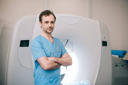 Photo for Smiling  radiologist standing near computed tomography scanner with crossed arms and looking at camera - Royalty Free Image