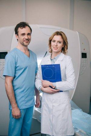 schöner Radiologe mit Klemmbrett, während er neben Assistent steht und in Kamera schaut