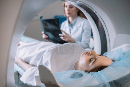 Photo pour Foyer sélectif du radiologiste tenant le diagnostic par rayons X tandis que le patient couché sur le lit ct scanner pendant les diagnostics - image libre de droit