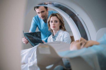 Selektiver Fokus der Ärzte mit Röntgendiagnose und Betrachtung der Frau während der Diagnostik auf dem Computertomographen