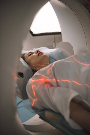 Photo pour Young woman lying on ct scanner bed during tomography diagnostics in hospital - image libre de droit