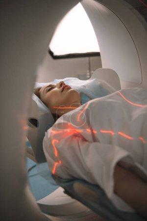 Photo pour Jeune femme couchée sur lit scanner ct lors de la tomographie diagnostics à l'hôpital - image libre de droit