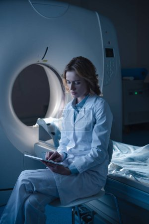 Photo for Thoughtful radiologist using digital tablet while sitting near computed tomography scanner - Royalty Free Image