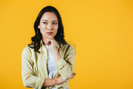 Photo for Pensive brunette asian girl isolated on yellow - Royalty Free Image