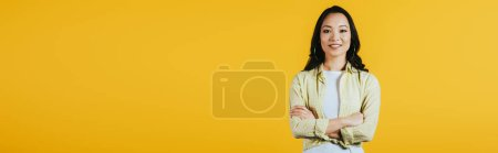 Photo for Smiling brunette asian girl with crossed arms isolated on yellow - Royalty Free Image