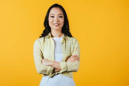 Photo pour Fille asiatique de sourire avec les bras croisés d'isolement sur le jaune - image libre de droit