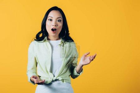Photo pour Jeune femme asiatique émotionnelle d'isolement sur le jaune - image libre de droit