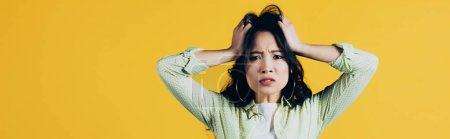 Photo for Worried asian woman holding head isolated on yellow - Royalty Free Image
