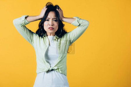 Photo for Beautiful stressed asian woman holding head isolated on yellow - Royalty Free Image