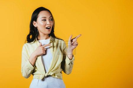 Photo pour Gai asiatique fille pointant vers quelque chose isolé sur jaune - image libre de droit
