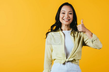 Photo for Attractive asian girl showing thumb up isolated on yellow - Royalty Free Image
