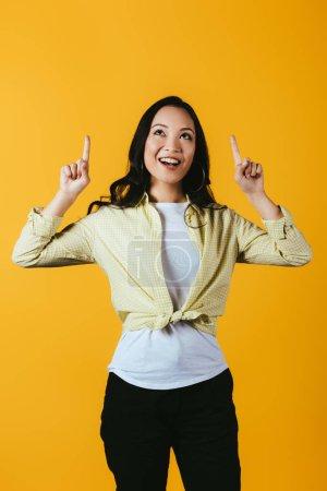 Photo pour Belle fille asiatique de sourire pointant vers le haut d'isolement sur le jaune - image libre de droit