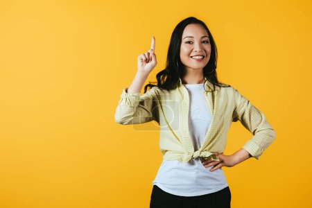 Photo for Attractive happy asian girl pointing up isolated on yellow - Royalty Free Image