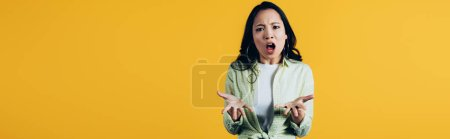 Photo for Aggressive emotional asian woman shouting isolated on yellow - Royalty Free Image