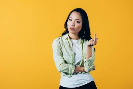 Photo pour Fille asiatique attirante pointant vers le haut d'isolement sur le jaune - image libre de droit