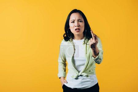 Photo pour Fille asiatique fâchée pointant vers le haut d'isolement sur le jaune - image libre de droit