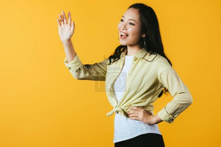 Photo pour Brunette asiatique fille agitant isolé sur jaune - image libre de droit