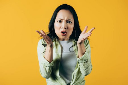 Photo for Beautiful angry asian woman gesturing isolated on yellow - Royalty Free Image