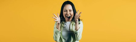 Photo for Angry asian woman gesturing and yelling isolated on yellow - Royalty Free Image