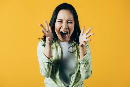 Photo pour Femme asiatique agressive faisant des gestes et criant isolé sur le jaune - image libre de droit