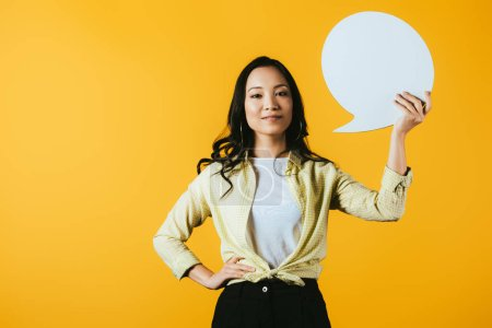Photo for Casual asian woman holding speech bubble, isolated on yellow - Royalty Free Image