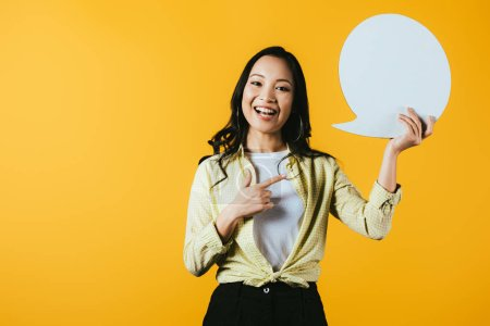 Photo for Casual asian woman pointing at speech bubble, isolated on yellow - Royalty Free Image