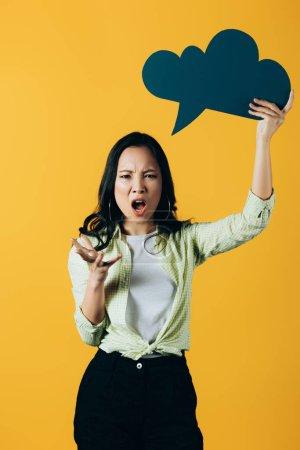 Photo pour Femme asiatique fâchée criant et retenant la bulle de discours de nuage, d'isolement sur le jaune - image libre de droit
