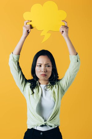 Photo for Sad asian woman holding cloud speech bubble, isolated on yellow - Royalty Free Image