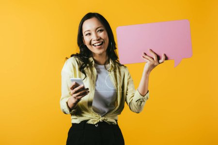 Photo pour Heureux asiatique fille en utilisant smartphone et tenant rose bulle de parole, isolé sur jaune - image libre de droit