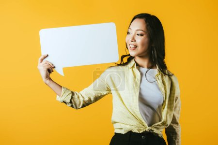 Photo for Happy asian woman holding speech bubble, isolated on yellow - Royalty Free Image