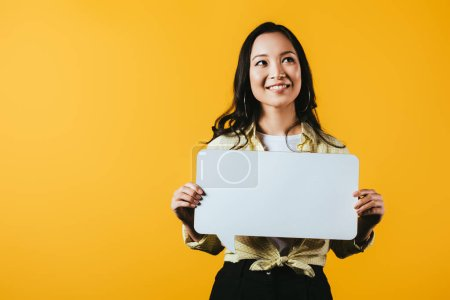 Photo for Smiling asian woman holding speech bubble, isolated on yellow - Royalty Free Image