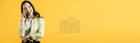 Photo pour Fille asiatique de sourire attirante parlant sur le smartphone d'isolement sur le jaune - image libre de droit