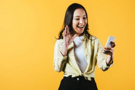 Photo pour Fille asiatique heureuse agitant et faisant l'appel vidéo sur le smartphone isolé sur le jaune - image libre de droit
