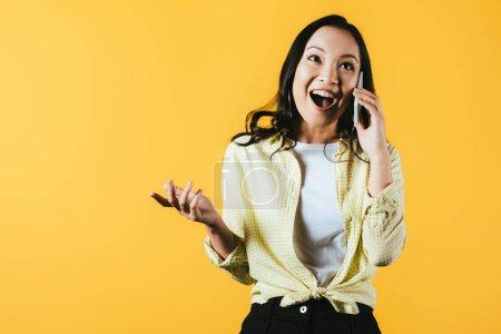Photo pour Fille asiatique excitée parlant sur le smartphone d'isolement sur le jaune - image libre de droit