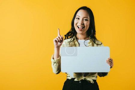 Photo pour Fille asiatique souriante retenant la bulle de discours et pointant vers le haut, d'isolement sur le jaune - image libre de droit