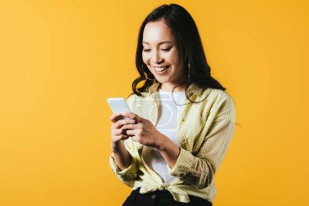 Photo pour Sourire asiatique fille en utilisant smartphone isolé sur jaune - image libre de droit