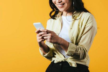 abgeschnittene Ansicht von glücklichen Mädchen mit Smartphone isoliert auf gelb