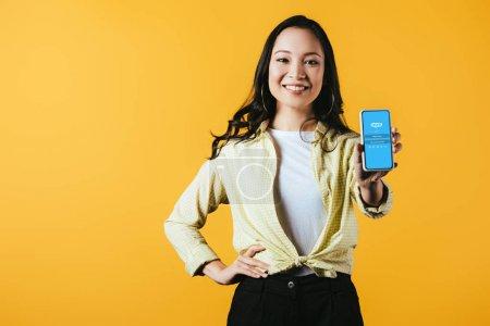 Photo pour Kiev, Ukraine - 16 avril 2019: fille asiatique souriante montrant smartphone avec l'application skype, isolée sur le jaune - image libre de droit