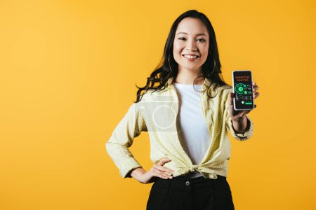 Photo pour Fille asiatique heureuse affichant le smartphone avec l'application d'analyse de marketing, d'isolement sur le jaune - image libre de droit