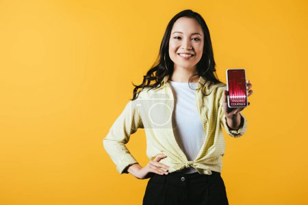 Photo for Happy asian girl showing smartphone with trading courses, isolated on yellow - Royalty Free Image