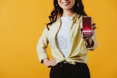 Photo pour Vue recadrée de fille de brunette affichant le smartphone avec l'application de cours de commerce, d'isolement sur le jaune - image libre de droit