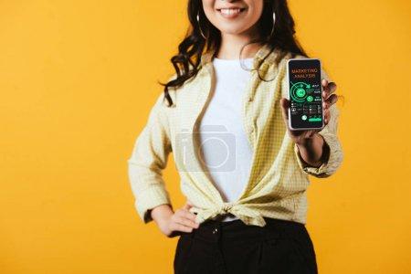 Photo pour Vue recadrée de fille de brunette affichant le smartphone avec l'analyse de marketing, d'isolement sur le jaune - image libre de droit