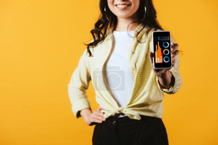 Photo for Cropped view of brunette girl showing smartphone with infographic, isolated on yellow - Royalty Free Image
