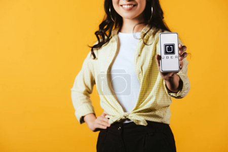 Photo for KYIV, UKRAINE - APRIL 16, 2019: cropped view of smiling girl showing smartphone with uber app, isolated on yellow - Royalty Free Image