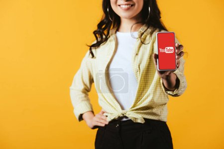 Photo for KYIV, UKRAINE - APRIL 16, 2019: cropped view of brunette girl showing smartphone with youtube app, isolated on yellow - Royalty Free Image