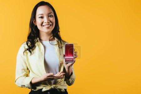 Photo pour Fille asiatique heureuse présentant le smartphone avec des cours de négociation, d'isolement sur le jaune - image libre de droit